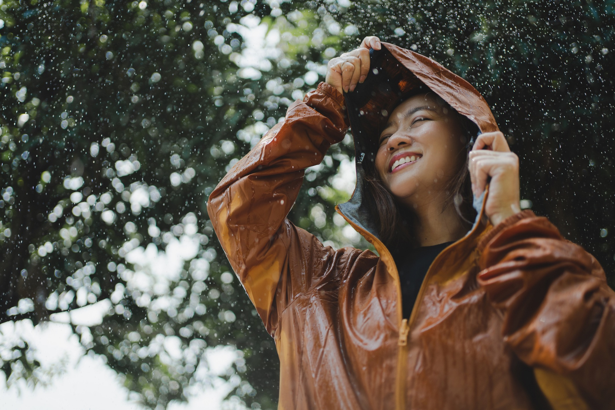 Asian woman is outdoors while it's raining. She felt refreshed.